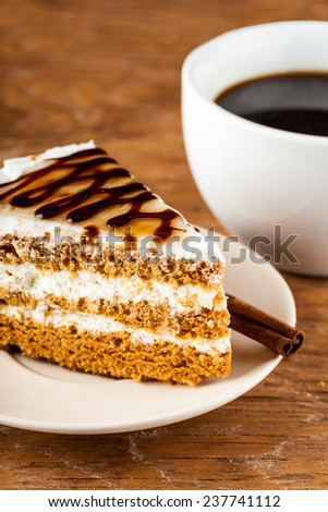 chocolate cake on a plate and black coffee on a wooden background
