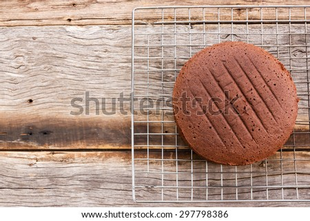 Chocolate cake on baking rack over wooden table. Top view.