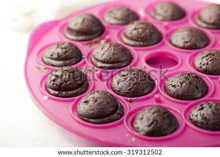 Chocolate cake pops in a baking tray, mold, dish on a white background. Process of cooking and decorating - stock photo