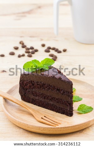 Chocolate cake slice in wooden plate on wood background. - stock photo