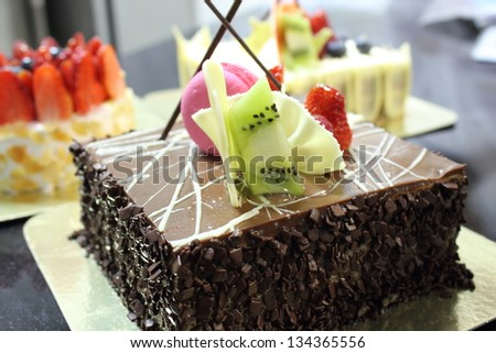 Chocolate cake topped with a strawberry and  kiwi - stock photo