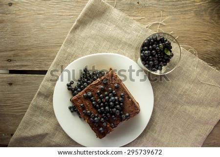 Chocolate cake with blueberry and glass with berries selective focus top view - stock photo