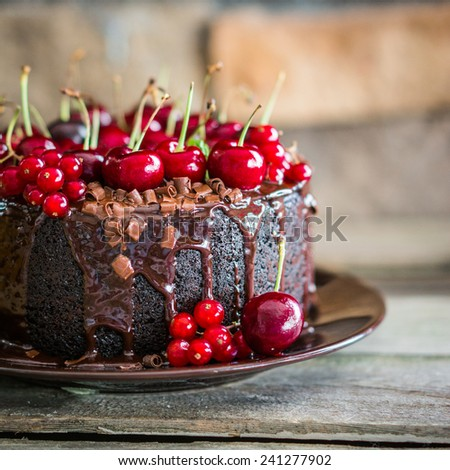 Chocolate cake with cherries on wooden background - stock photo