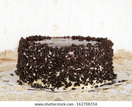 Chocolate Cake with Chocolate, Cake isolated on warm light background with selective focus. Birthday cake in blur decorated background - stock photo