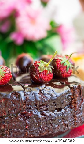 Chocolate cake with chocolate icing on a background of flowers - stock photo