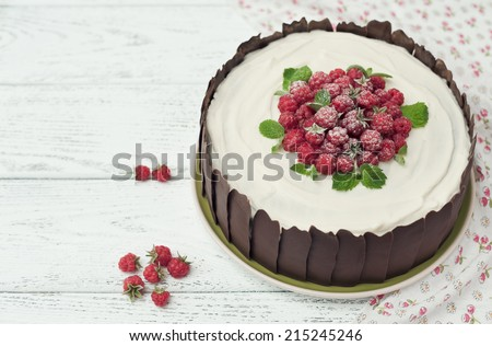 Chocolate cake with cream and raspberries on wooden background - stock photo