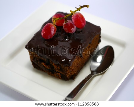 chocolate cake with fresh grapes on white isolated background