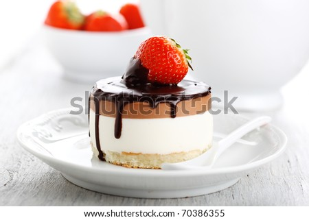 Chocolate cake with fresh strawberry on white plate - stock photo