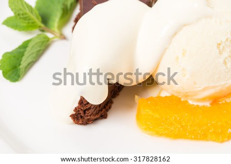 Chocolate cake with ice cream scoop on a sliced orange and mascarpone. Macro. Photo can be used as a whole background. - stock photo