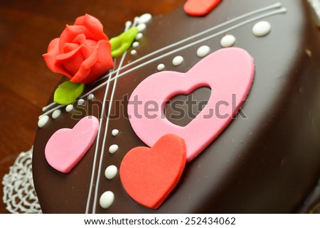 Chocolate cake with pink hearts and red rose decorations - stock photo