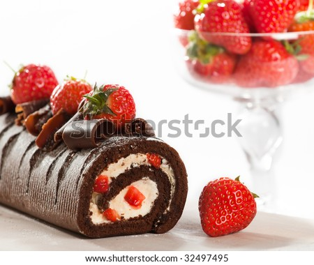 Chocolate cake with strawberries and glass bowl of fruit in background - stock photo
