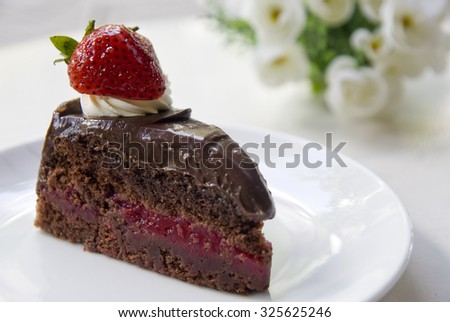 chocolate cake with strawberry on white dish.