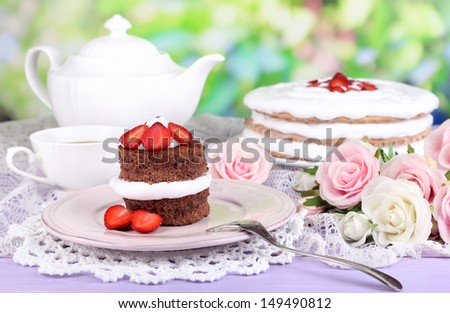 Chocolate cake with strawberry on wooden table on natural background