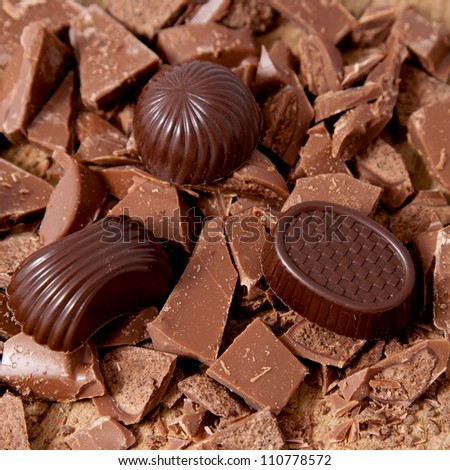 Chocolate candies of different shapes and broken pieces of milk chocolate. Delicious food background. Selective focus on the candies - stock photo