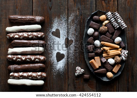 Chocolate candies set flat lay on dark wooden table background. Bunch of candies on black dish. Table decorated with sugar powdered hearts top view - stock photo