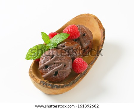 Chocolate candies with raw raspberries on wooden background