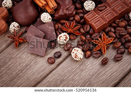 Chocolate candies with spices and coffee bean on wooden background