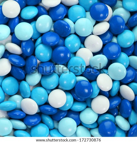 Chocolate candy coated in blue and white. Background - stock photo