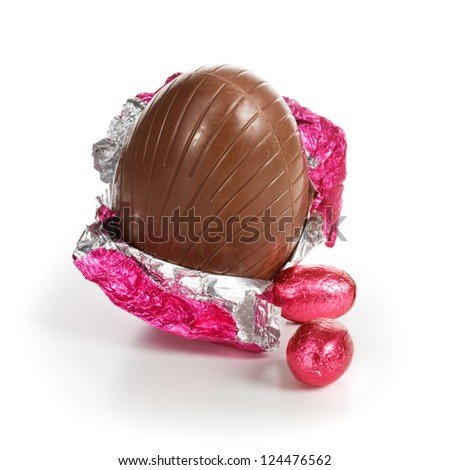 Chocolate candy Easter eggs wrapped in pink foil on white background - stock photo