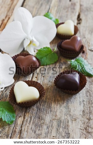 chocolate candy in the form of hearts and flowers orchid on a wooden background. selective focus - stock photo