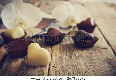 chocolate candy in the form of hearts, flowers and old photos on a wooden background. toned picture in retro style. selective focus - stock photo