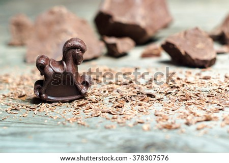 Chocolate candy in the shape of a horse on the background pieces of chocolate. Shallow DOF - stock photo