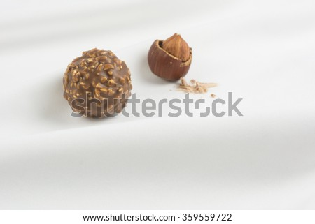 Chocolate candy with hazelnut on beautiful white material