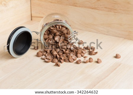 Chocolate cereal cornflakes spilling out from the glass jar - stock photo