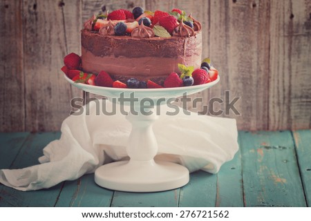Chocolate cheesecake and devil food layer cake with fresh berries toned image - stock photo
