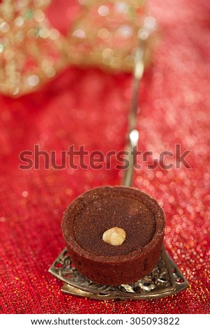 Chocolate Cherry Mini Tartlets in vintage spoon with festive golden red style, shallow dof - stock photo