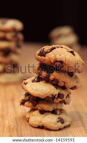 Chocolate chip cookie towers on a wooden chopping block.