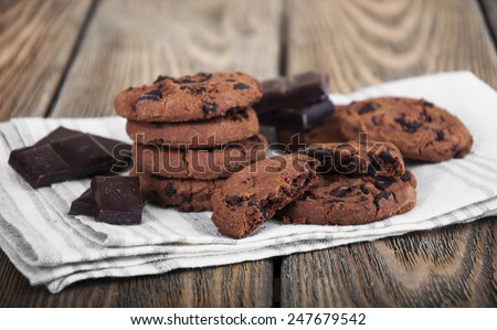 Chocolate chip cookies and chocolate on linen napkin on wooden background - stock photo