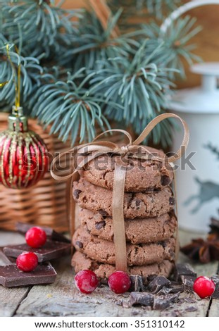 Chocolate chip cookies, cranberry and chocolate. Christmas gifts. Round cookies, tied with ribbon and spruce branch in a basket on the table - stock photo