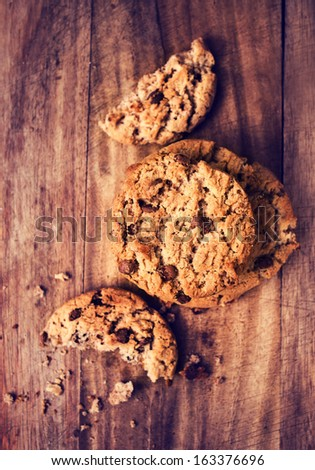 Chocolate chip cookies pile shot on wooden table, top view. Chocolate cookies over wooden background in country style.   - stock photo
