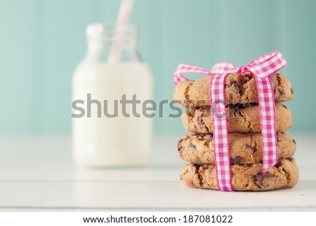 Chocolate chip cookies with a pink ribbon and a school milk bottle with a straw on a white wooden table with a robin egg blue background. Vintage look. - stock photo