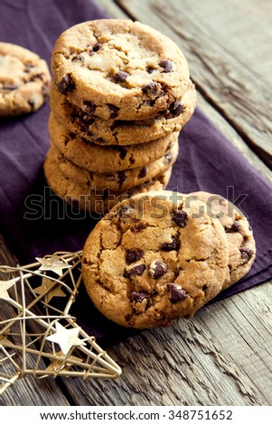 Chocolate chip cookies with Christmas star on brown napkin and rustic wooden table