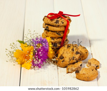 chocolate chips cookies with red ribbon and wildflowers on wooden table