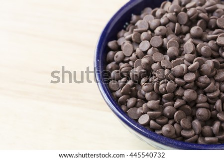 Chocolate chips in blue bowl close up with copy space