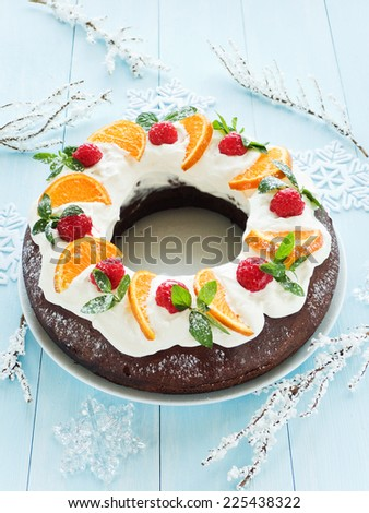 Chocolate Christmas cake with tangerines, raspberry and whipped cream. Shallow dof. - stock photo