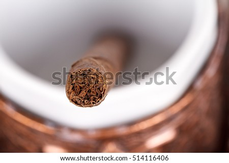Chocolate cigar in traditional Turkish coffee cup.