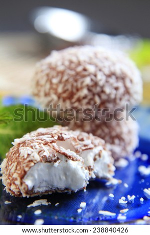 Chocolate-coated marshmallow treats with a sprinkle of coconut - stock photo