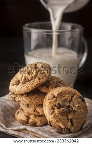 chocolate cookie with milk on wooden table - stock photo