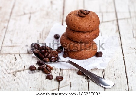 chocolate cookies and spoon with coffee beans on rustic wooden background - stock photo