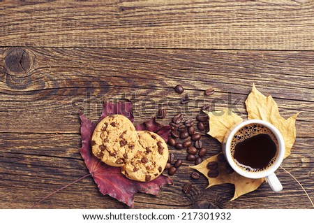 Chocolate cookies, cup of hot coffee and autumn leaves on wooden background. Top view - stock photo