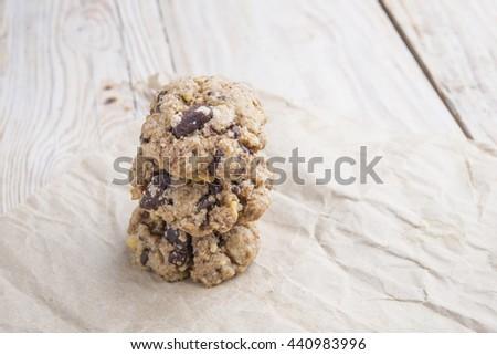 Chocolate cookies on white linen napkin on wooden table - stock photo