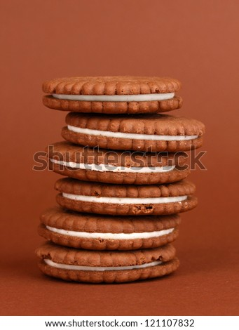 Chocolate cookies with creamy layer on brown background