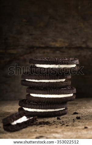 Chocolate Cookies with Vanilla Cream Filling over wooden background - stock photo