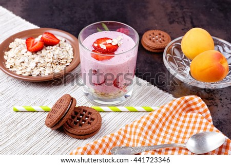 Chocolate cookies, yogurt smoothie with berries and cereal, strawberries, raspberries, half of apple and apricots on the table. Sweet pink milk-berry cocktail, straw, berries and cereals. - stock photo
