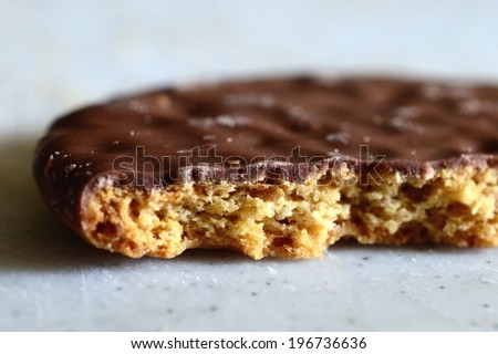 Chocolate-covered cookie or biscuit with crumbly texture. - stock photo