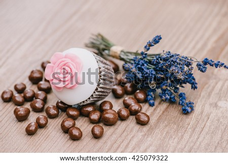 Chocolate covered espresso coffee beans ready to eat with a muffin and lavander - stock photo